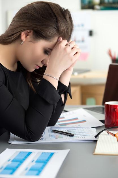 Zmęczona Pracownica W Miejscu Pracy W Biurze Dotykając Jej Głowy. śpiący Pracownik Wcześnie Rano Po Pracy W Nocy. Koncepcja Przepracowania, Popełniania Błędów, Stresu, Wypowiedzenia Lub Depresji Premium Zdjęcia
