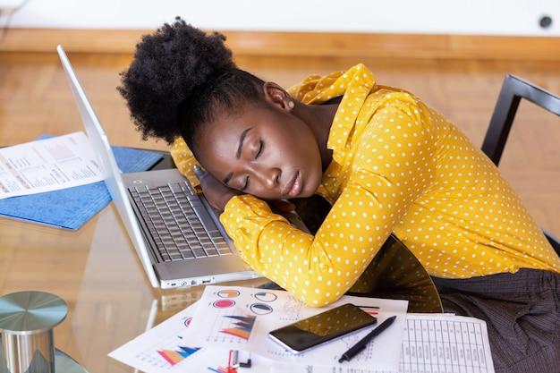 Zmęczona Przepracowana Kobieta Odpoczywa Podczas Pisania Notatek. Zapracowany I Zmęczony Bizneswoman śpi Nad Laptopem W Biurku W Domu. Zmęczony Bizneswoman Premium Zdjęcia