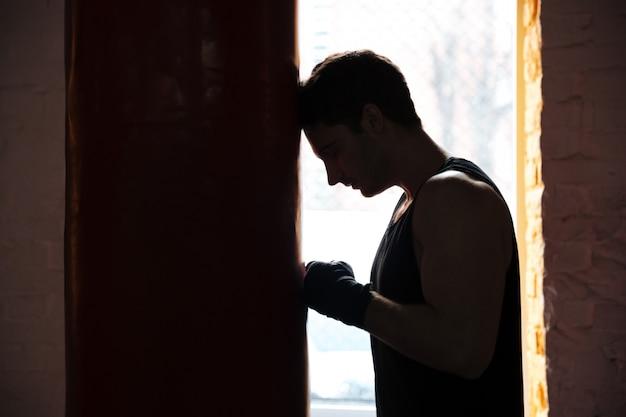 Zmęczony Mężczyzna Sportowca, Opierając Się Na Punchbag Podczas Treningu Darmowe Zdjęcia