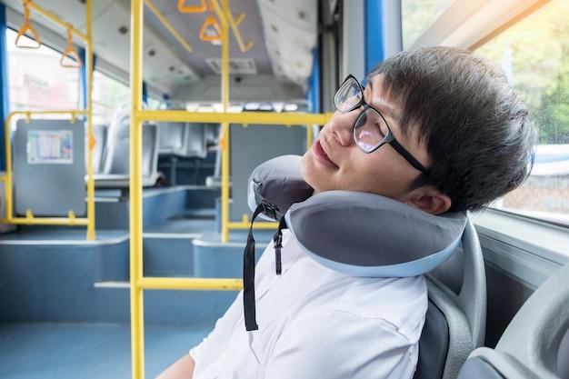 Zmęczony mężczyzna wygodnie w autobusie i spanie z nadmuchiwaną poduszką na szyję szyjkową, transport Premium Zdjęcia