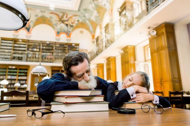 Zmęczony Starszy Profesor Nauczyciel Brodaty I Jego Uczeń Lub Wnuczka śpią W Bibliotece Leżącej Na Stole Premium Zdjęcia