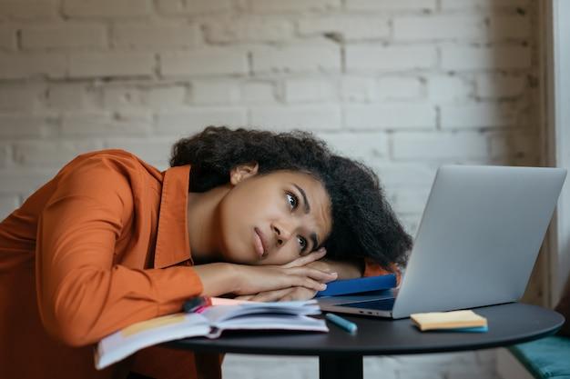 Zmęczony Student śpi Na Książkach, Przepracowanie. Wyczerpana Kobieta Po Ciężkiej Pracy, Wielozadaniowość. Sfrustrowany, Smutny Freelancer Nie Dotrzymał Terminu Premium Zdjęcia