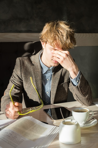 Zmęczony Student Zdejmuje Okulary I Pociera Oczy Podczas Przerwy Kawowej W Restauracji Premium Zdjęcia