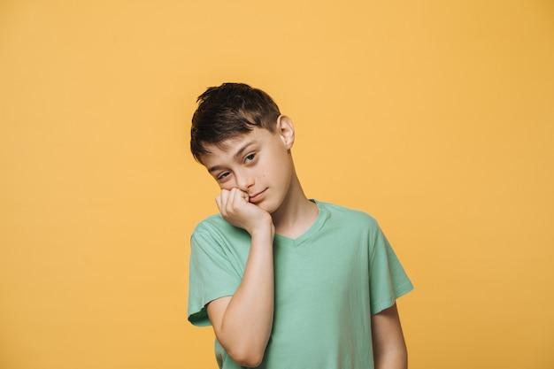 Zmęczony Szkolny Chłopiec O Brązowych Oczach Ubrany W Zielony T-shirt, Ręcznie Podpiera Głowę, Ma Mało Energii Po Wielu ćwiczeniach. Koncepcja Edukacji I Młodzieży. Premium Zdjęcia