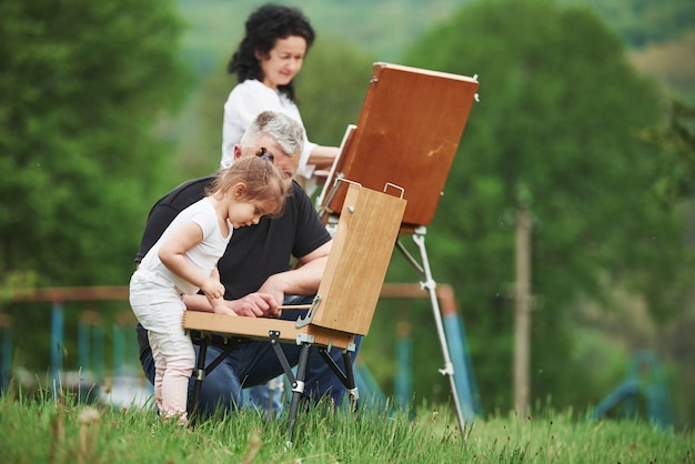 Zmieniające Się Kolory. Babcia I Dziadek Bawią Się Na świeżym Powietrzu Z Wnuczką. Koncepcja Malarstwa Darmowe Zdjęcia