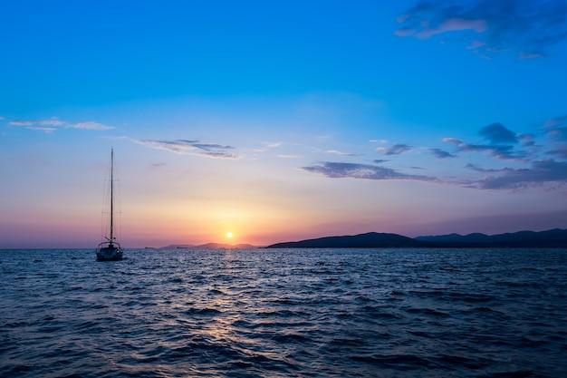 Zmierzch W Morzu Z żaglówką Na Horyzoncie. Horyzont Morski. Premium Zdjęcia