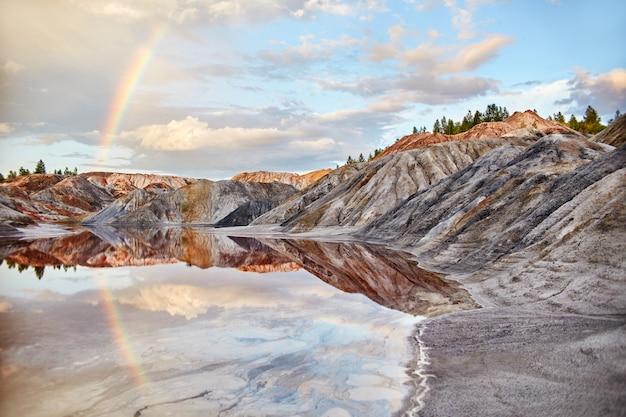 Zmierzch z tęczą w piasków wzgórzach. bajkowy magiczny krajobraz. piękne kolorowe góry, jeziorny kolor czerwony Premium Zdjęcia