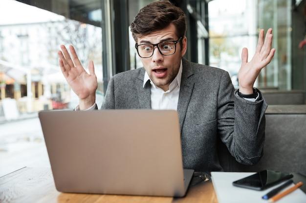 Zmieszany Biznesmen Siedzi Stołem W Kawiarni I Patrzeje Laptop W Eyeglasses Darmowe Zdjęcia