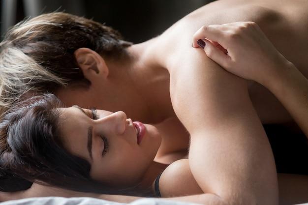 Zmysłowa para seks, kobieta obejmując kochanka leżąc na łóżku Darmowe Zdjęcia
