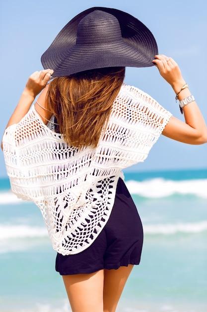 Zmysłowy Portret Mody Letniej Eleganckiej Pani W Kapeluszu I Eleganckim Stroju Boho Pozuje Na Niesamowitej Tropikalnej Plaży Z Błękitnym Czystym Morzem. Nie Spoglądaj Na Ocean I Ciesz Się Jej Wakacjami Darmowe Zdjęcia