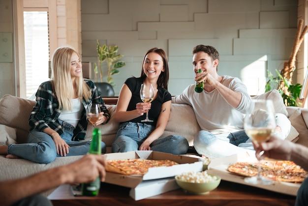 Znajomi Z Pizzą, Winem I Piwem Rozmawiają I Dobrze Się Bawią Premium Zdjęcia