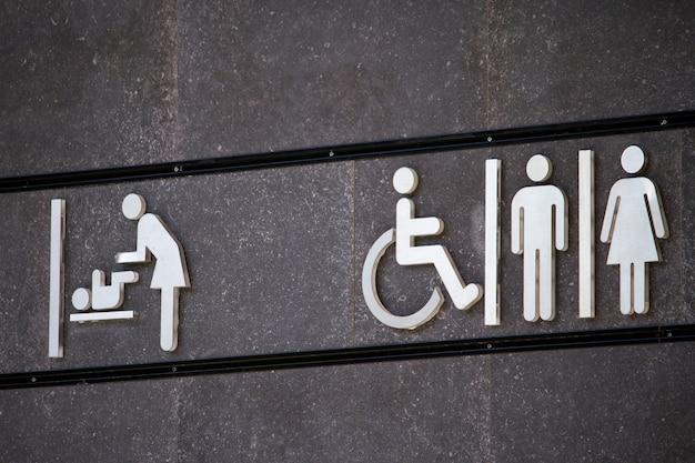 Znak Toalety Dla Wszystkich Płci I Osób Niepełnosprawnych, Znak Szatni, Minimalny Projekt Znaku Na Szarej ścianie, Selektywne Ustawianie Ostrości Premium Zdjęcia