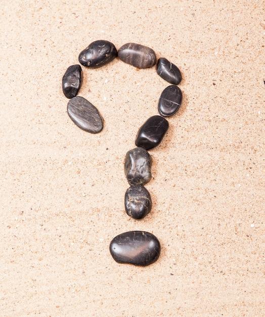 Znak zapytania rysowane z kamykami na piasku plaży Premium Zdjęcia