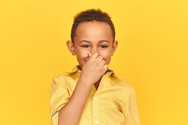 Zniesmaczony, Niezadowolony Ciemnoskóry Chłopiec Szczypie Nos Palcami, Wstrzymując Oddech Z Powodu Nieprzyjemnego, Obrzydliwego Smrodu Spoconych Pach Lub Brudnych Skarpet Darmowe Zdjęcia