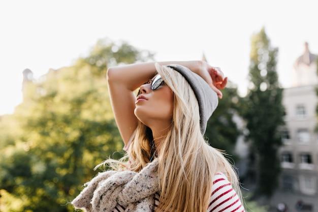 Znudzona Blondynka W Kapeluszu I Szaliku, Patrząc W Niebo Podczas Spaceru Po Ulicy Darmowe Zdjęcia