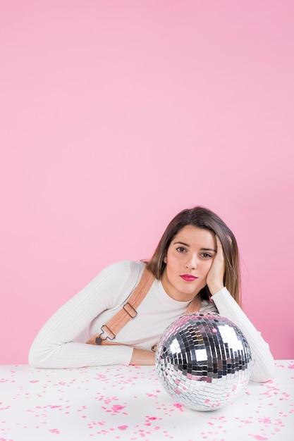 Znudzona kobieta siedzi przy stole z błyszczącą kulę disco Darmowe Zdjęcia