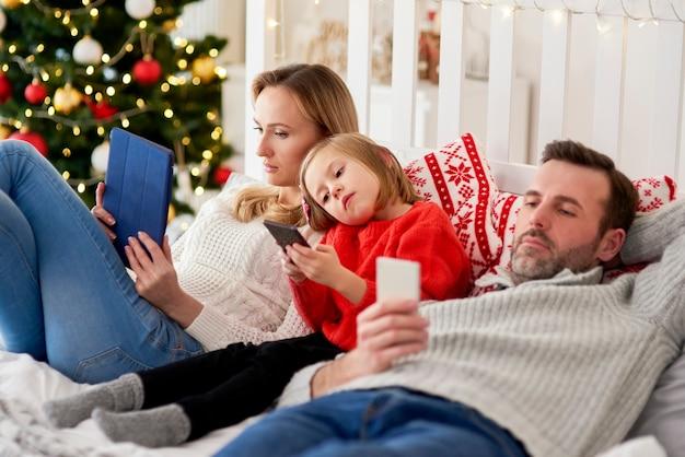 Znudzona Rodzina Przy Użyciu Telefonu Komórkowego W łóżku Na Boże Narodzenie Darmowe Zdjęcia