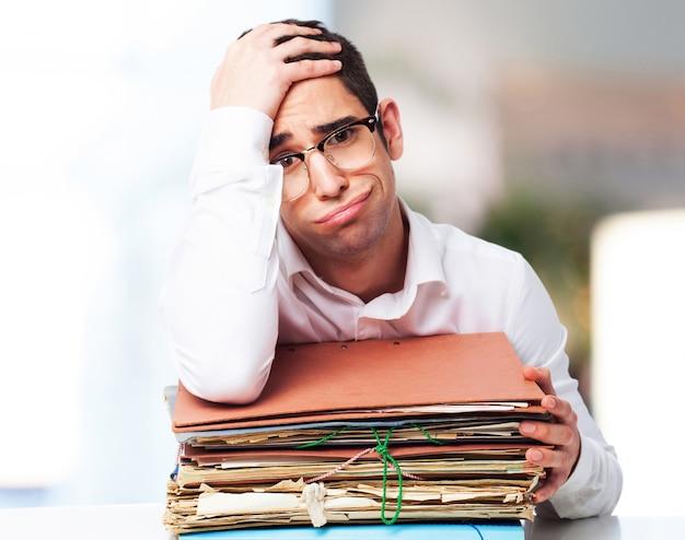 Znudzony Człowiek Patrząc Na Stos Papierów Z Jednej Strony Na Czole Darmowe Zdjęcia