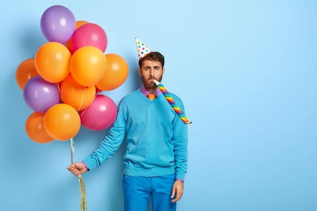 Znudzony Facet Z Urodzinową Czapką I Balonami, Pozowanie W Niebieskim Swetrze Darmowe Zdjęcia