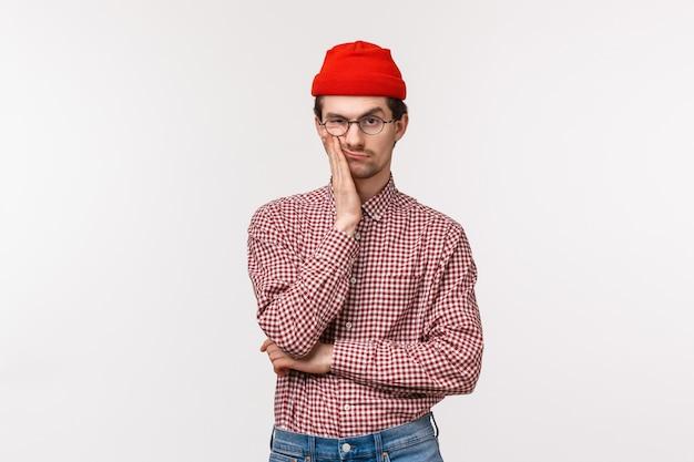 Znudzony I Sceptyczny Sceptyczny Portret Młodego Mężczyzny W Czerwonej Czapce, Okularach, Twarzy I Uśmieszku, Krzywiący Się, Robi Zirytowany Wyraz, Widząc Coś Naprawdę Głupiego Premium Zdjęcia