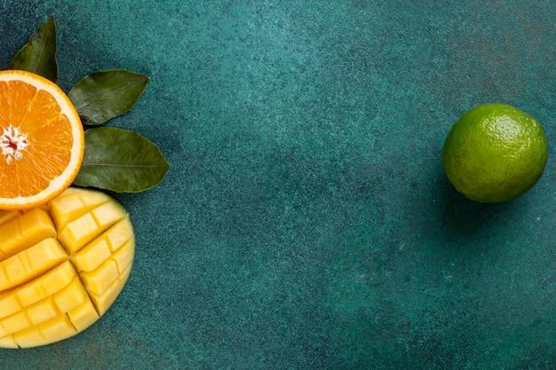 Zobacz Kopię Miejsca Pokrojone Mango Z Połową Pomarańczy I Bananów Na Zielonym Stole Darmowe Zdjęcia