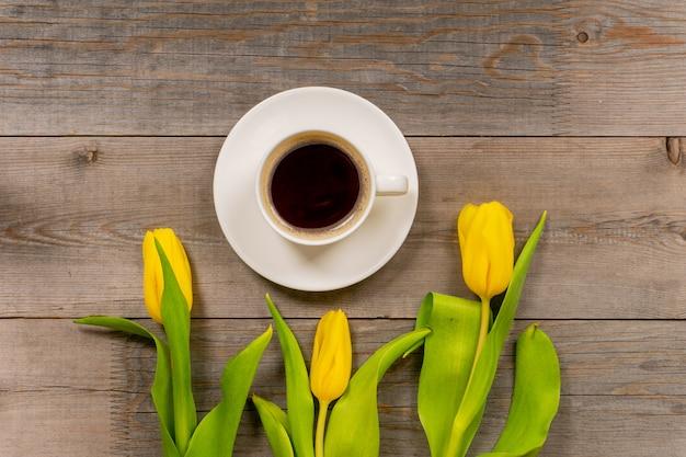 Żółci Tulipany I Filiżanka Kawy Na Nieociosanym Drewnianym Stole. Widok Z Góry Z Miejsca Kopiowania. Premium Zdjęcia