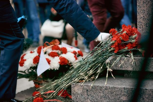 Żołnierz W Białych Rękawiczkach Kładzie Kwiaty Pod Pomnikiem żołnierzy Poległych Podczas Ii Wojny światowej Premium Zdjęcia
