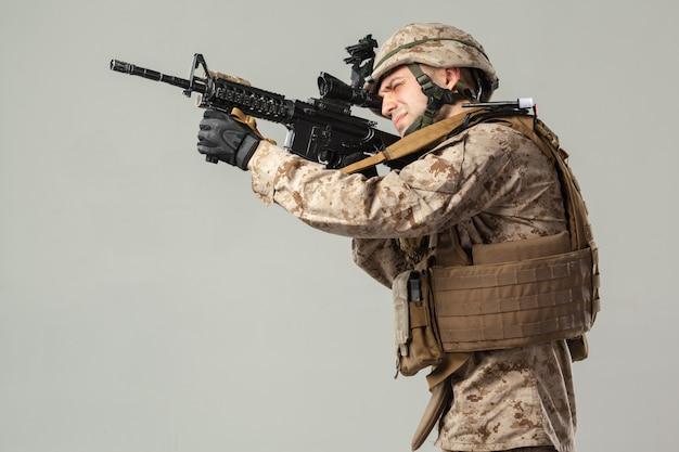Żołnierz w kamuflażu trzyma karabin Premium Zdjęcia