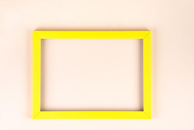 Żółta rama odizolowywająca na beżowym tle z copyspace, mieszkanie nieatutowy Premium Zdjęcia