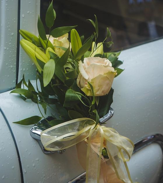 Żółta róża z ozdobnymi kwiatami w rękojeści białego luksusowego samochodu Darmowe Zdjęcia