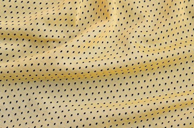 Żółta sporta bydła odzieży tkaniny tekstura i tło z wiele fałdami Premium Zdjęcia