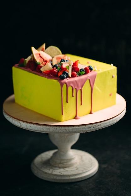 Żółte Ciasto Cytrusowe Ozdobione Figami, Malinami, Jagodami I Cytryną. Premium Zdjęcia