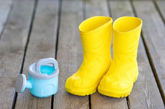 Żółte Gumowe Buty I Konewka Dla Dzieci Na Desce Premium Zdjęcia