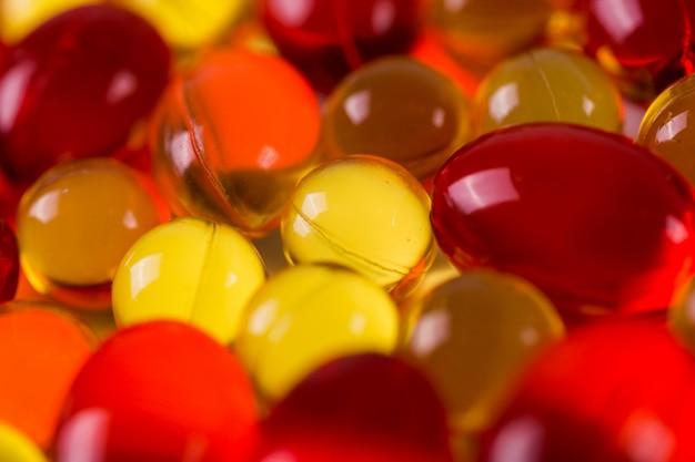 Żółte I Czerwone Kapsułki Medyczne Na Powierzchni Lustra Premium Zdjęcia