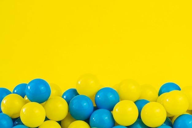 Żółte i niebieskie plastikowe kulki w basenie pokoju gier Premium Zdjęcia