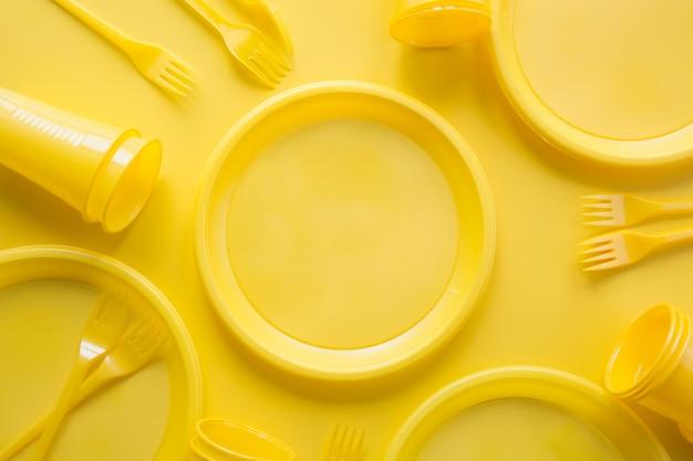 Żółte jednorazowe przybory piknikowe. ocal planetę. Premium Zdjęcia