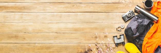 Żółte Kalosze, Plecak, Lornetka, Kurtka, Sprzęt Kempingowy Na Drewnianym Tle. Koncepcja Turystyki Pieszej, Turystyki, Obozu, Gór, Lasu. Premium Zdjęcia