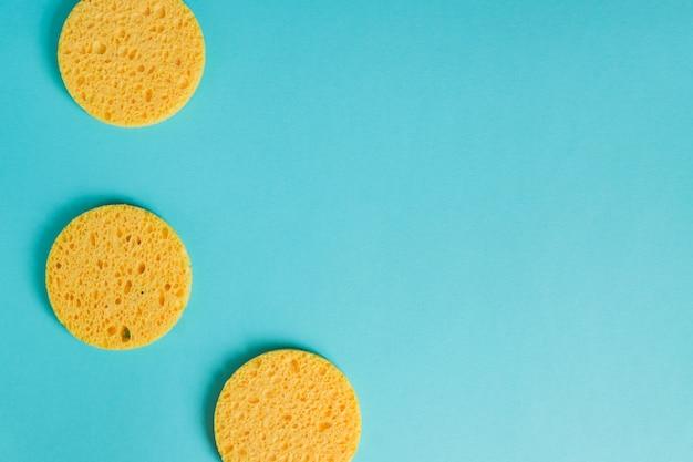 Żółte Okrągłe Gąbki Na Pastelowym Niebieskim Tle, Pielęgnacja Twarzy. Urządzenie Kosmetyczne. Głębokie Oczyszczenie Skóry. Premium Zdjęcia