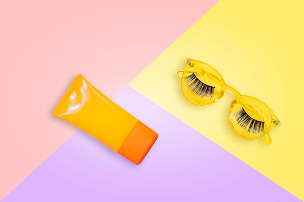 Żółte Okulary Z Fałszywymi Rzęsami I Pomarańczowym Kremem Przeciwsłonecznym Spf Krem Na Różowym Tle. Premium Zdjęcia