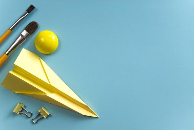 Żółte pędzle i papierowy samolot do inspiracji Darmowe Zdjęcia