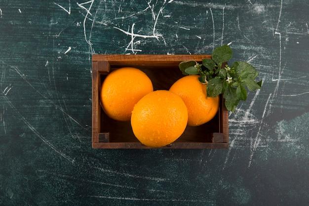 Żółte Pomarańcze Z Zielonymi Liśćmi W Drewnianym Pudełku Pośrodku Darmowe Zdjęcia