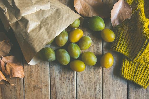 Żółte Zielone śliwki W Brown Kraft Paper Bag Rozproszone Premium Zdjęcia