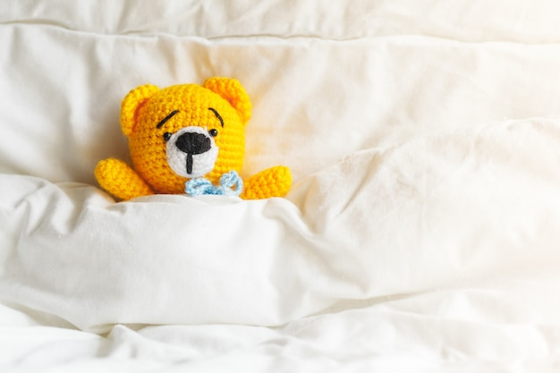 Żółty Chory Miś Leży W łóżku Na Białym Tle. Premium Zdjęcia