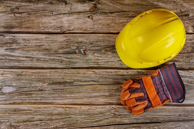 Żółty Ciężkiego Bezpieczeństwa Odzieży Hełma Kapelusz W Budowy Pracy Rzemiennych Rękawiczkach W Drewnianym Tle Premium Zdjęcia