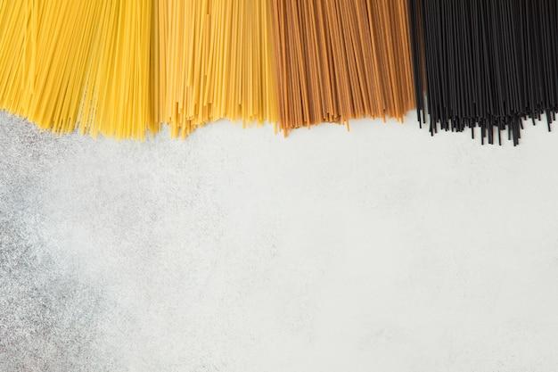 Żółty Długi Spaghetti Na Szarym Tle. Włoski Makaron Z Różnych Odmian Pszenicy I Różnych Kolorów. Odgórny Widok Surowy Spaghetti, Karmowy Tła Flatlay Pojęcie. Premium Zdjęcia