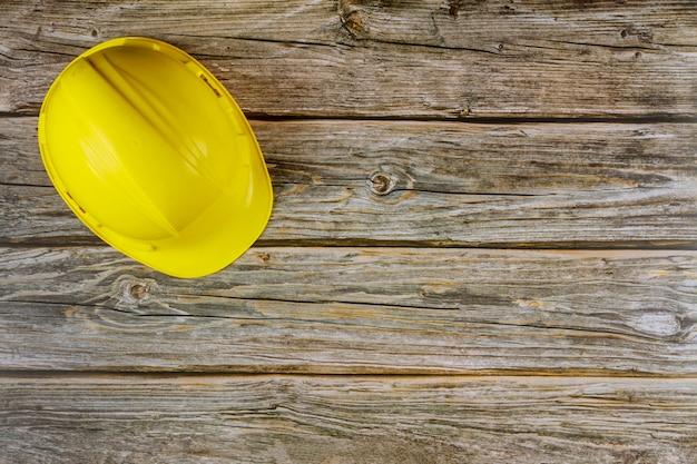 Żółty Kask Bezpieczeństwa Na Budowie Z Drewnianym Stołem. Premium Zdjęcia