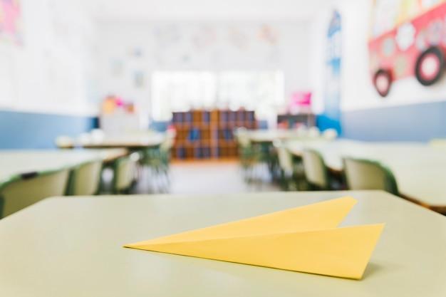 Żółty papierowy samolot na biurku w klasie Darmowe Zdjęcia
