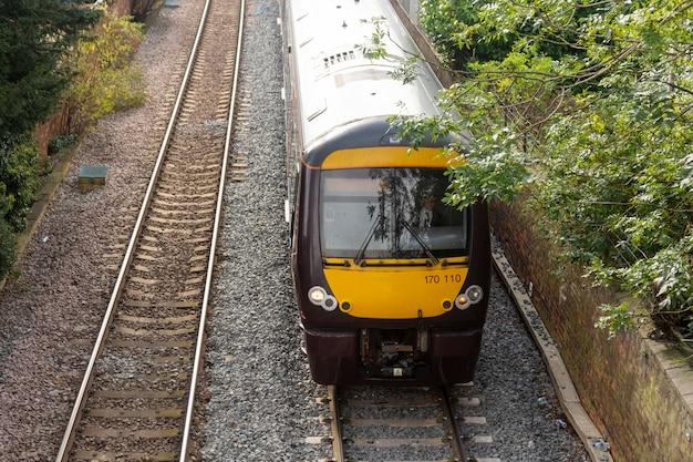 Żółty pociąg, stacja kolejowa. transport publiczny. Premium Zdjęcia
