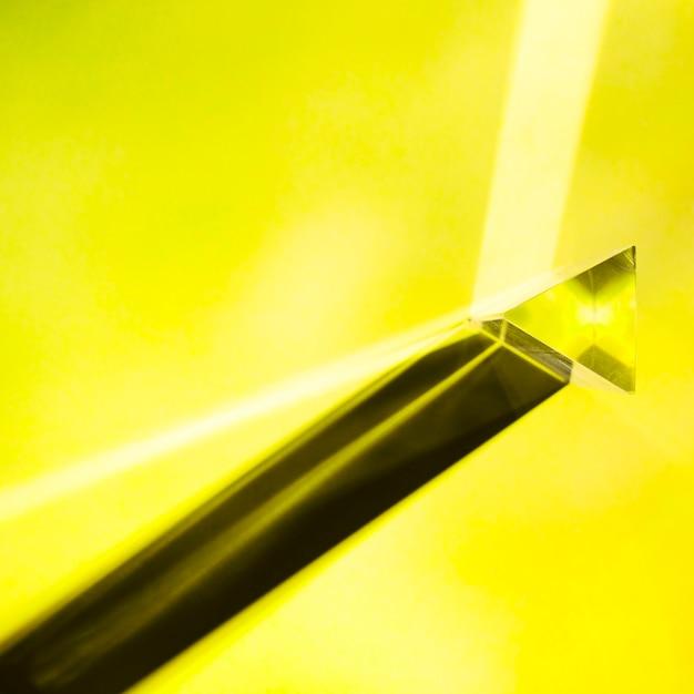 Żółty Trójkątny Kryształ Z Cieniem Na żółtym Tle Darmowe Zdjęcia