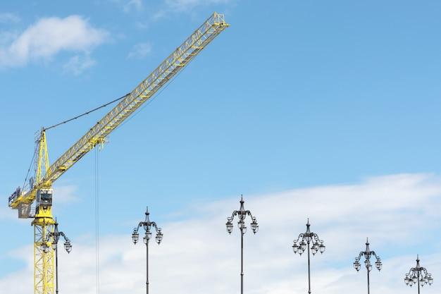 Żółty żuraw Przeciw Niebu I Latarniom Ulicznym. Premium Zdjęcia